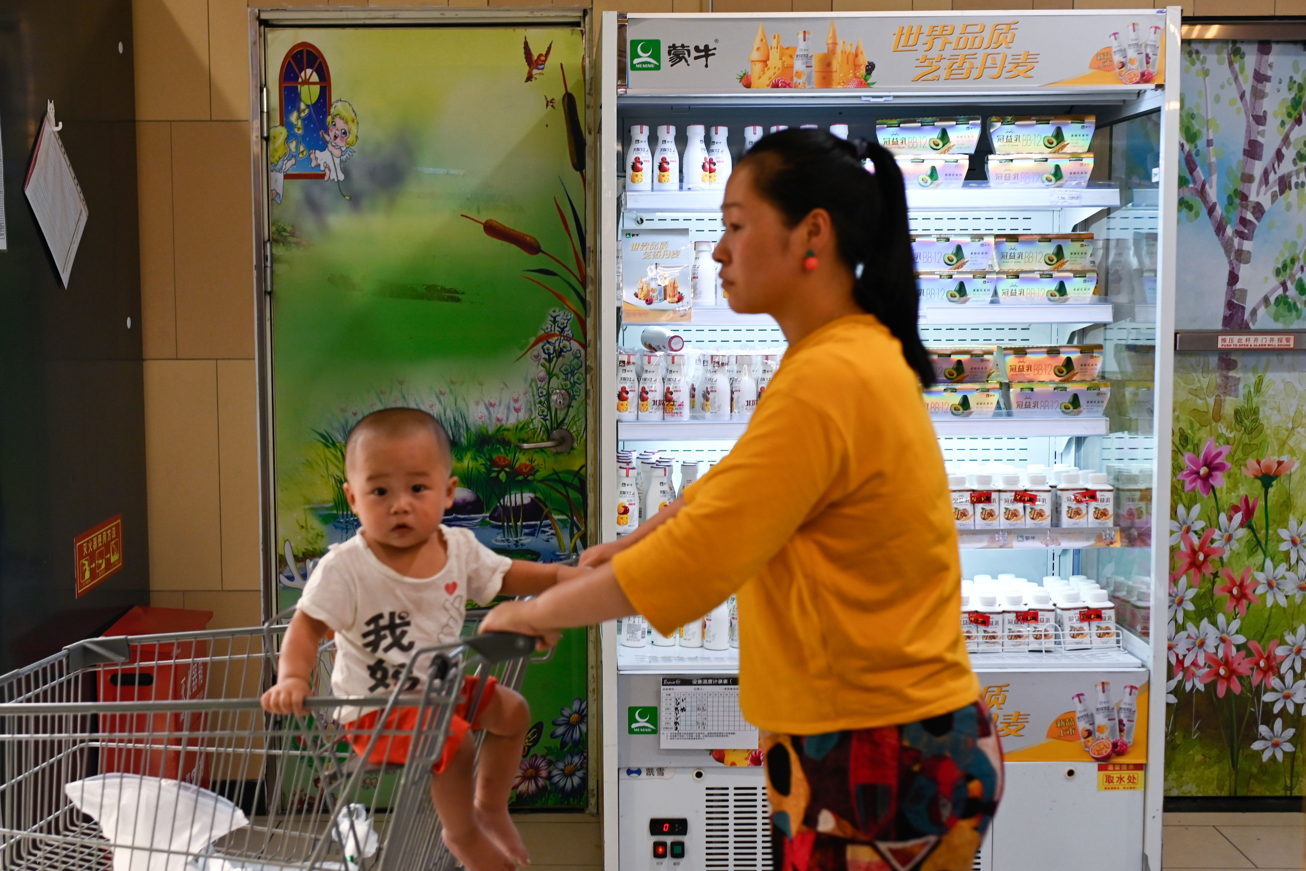 A customer and child are seen past a refrigerator displaying Mengniu milk products at a store in Beijing on June 24, 2019. - Coca-Cola and Chinese dairy firm Mengniu have signed a deal to become joint sponsors of the Olympic Games from 2021 to 2032, IOC chief Thomas Bach announced on June 24. (Photo by WANG Zhao / AFP) (Photo credit should read WANG ZHAO/AFP/Getty Images)