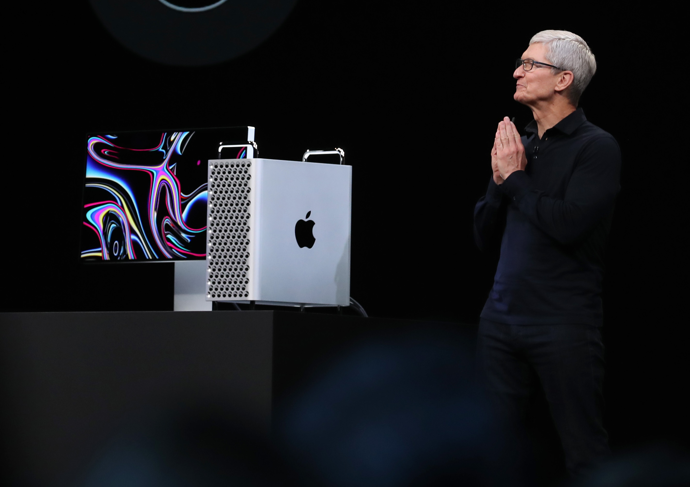 Tim Cook stands with hands pressed together next to the new Mac Pro, against a black background.