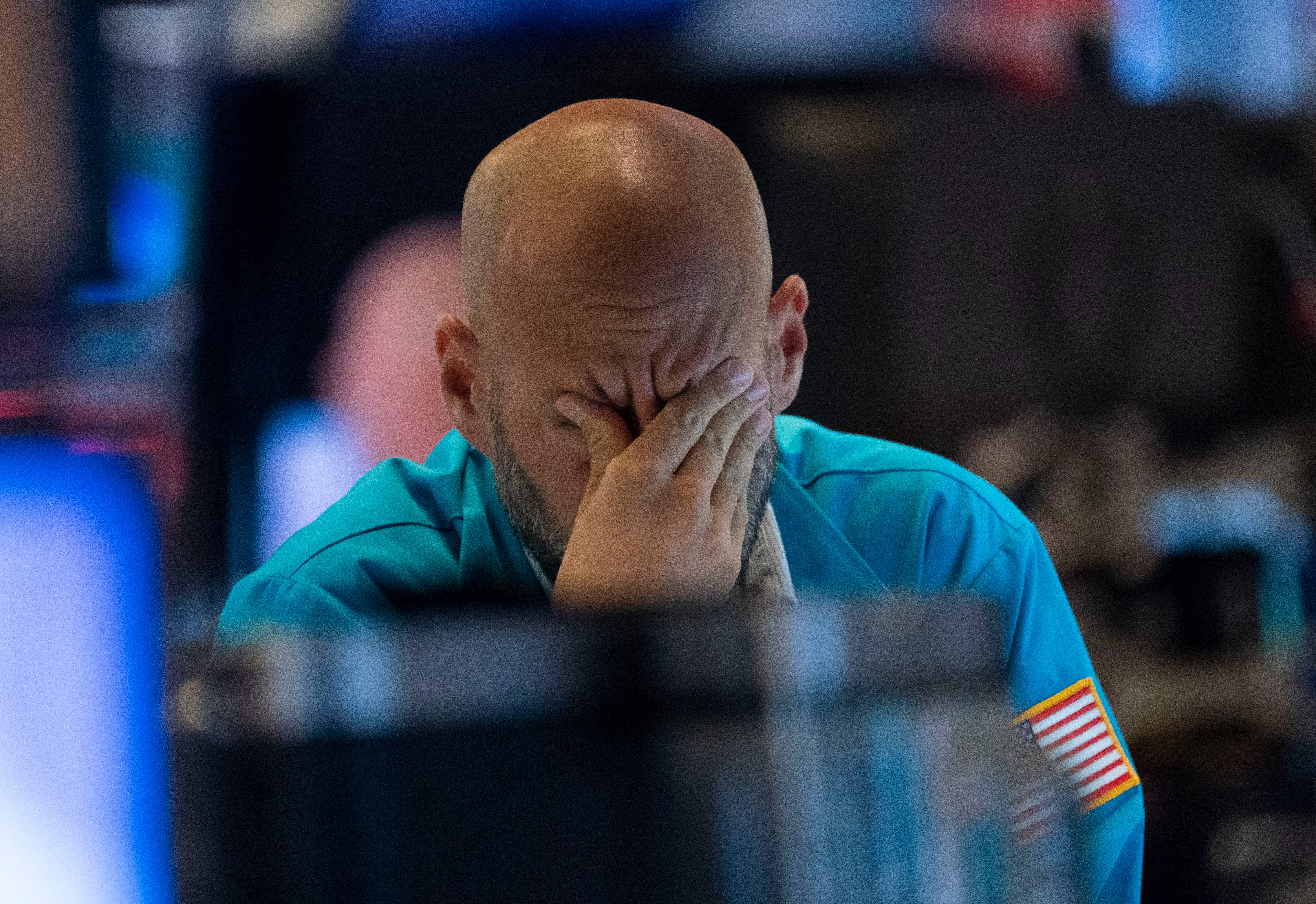 A trader wipes his eyes as he watches stock prices at the New York Stock Exchange August 23, 2019 in New York. - Wall Street stocks tanked Friday after President Donald Trump vowed a tough response to new Chinese tariffs, escalating the trade war between the world's top two economies amid rising fears of recession. The Dow Jones Industrial Average sank more than 600 points, or 2.4 percent, to 25,628.90, registering its fourth straight weekly loss.