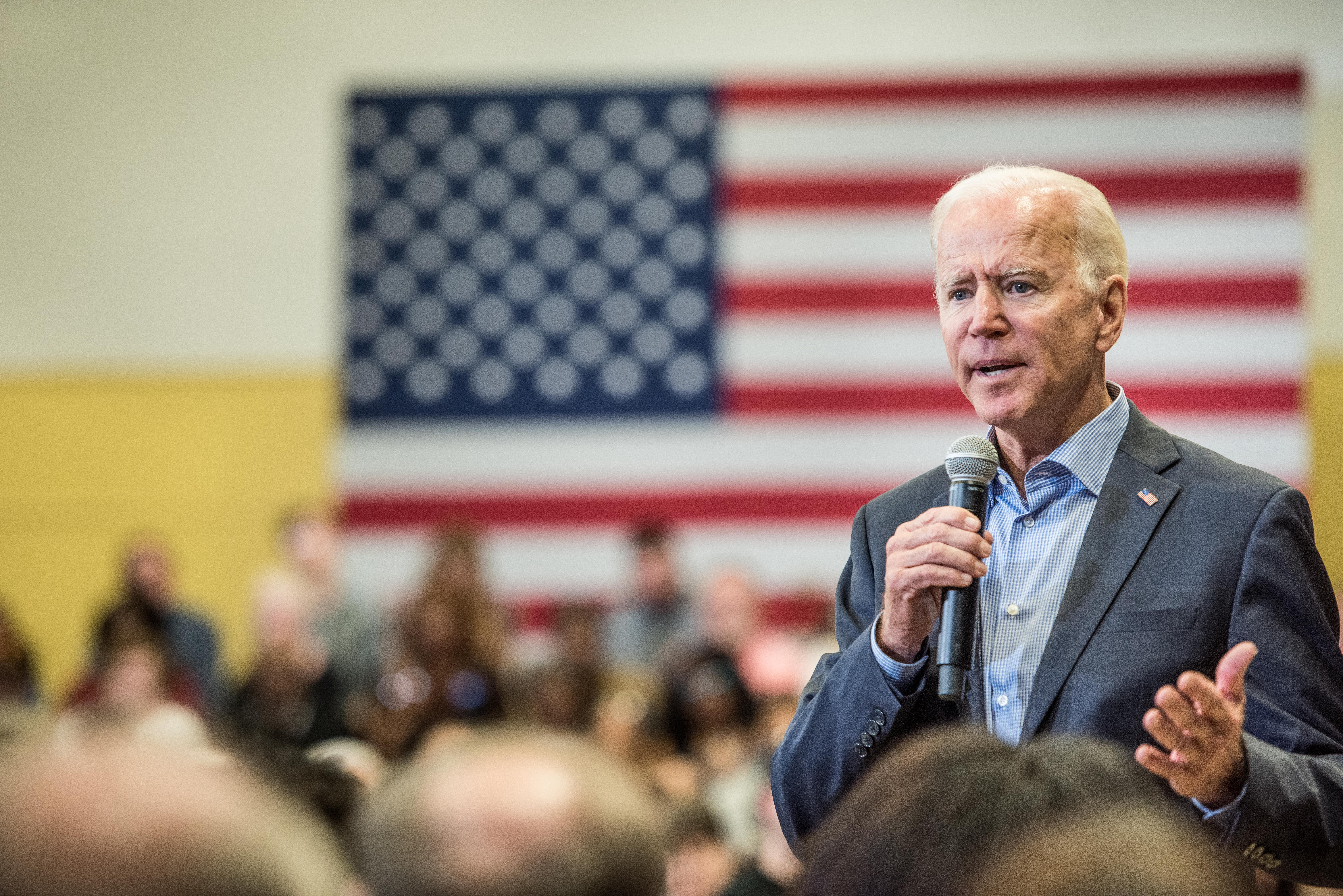 Joe Biden speaks into a microphone in front of a crowd with an American flag in the background.