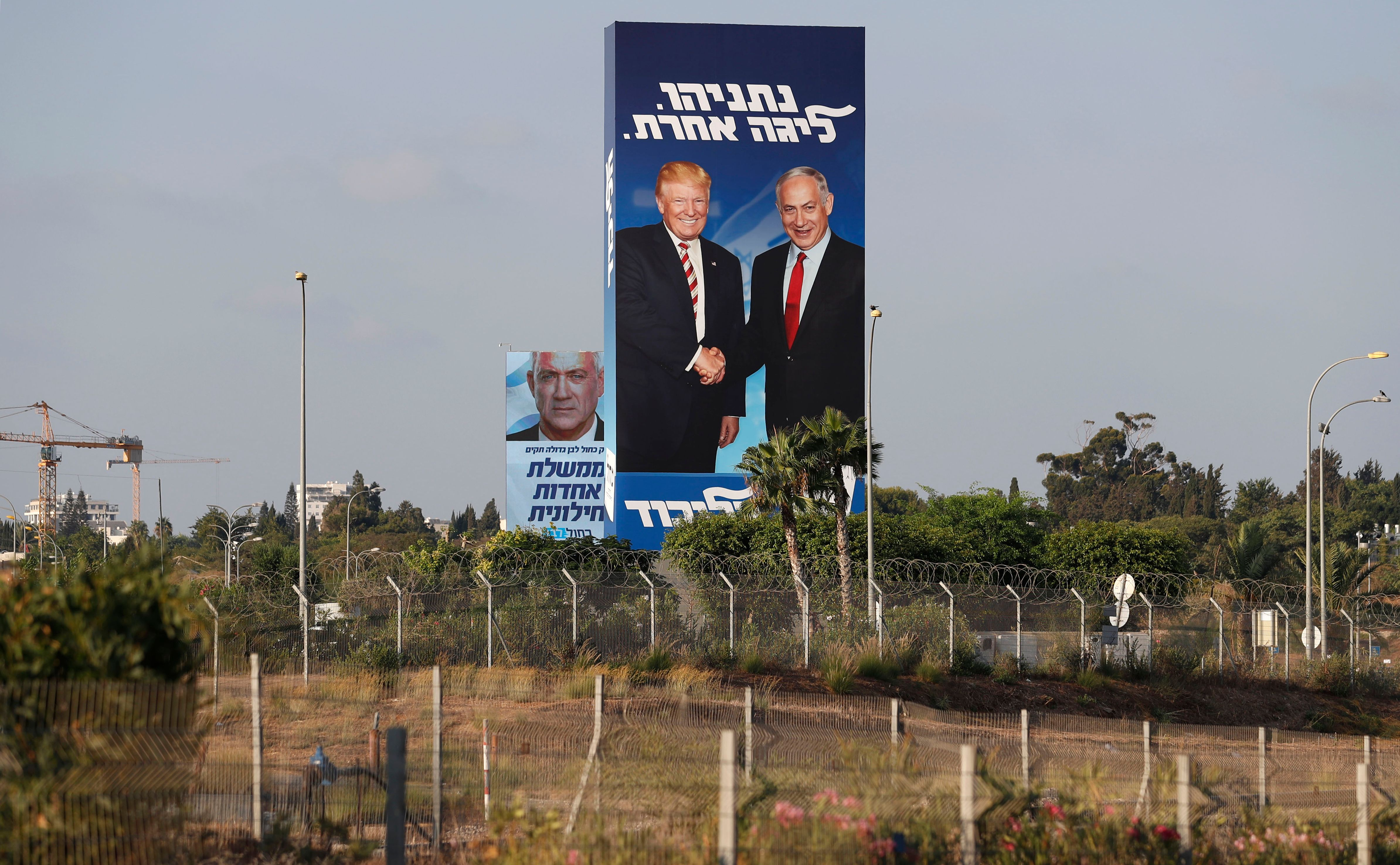 """This picture taken on September 9, 2019 shows Israeli election billboards in the Israeli coastal city of Tel Aviv (R to L) for the Likud party showing US President Donald Trump shaking hands with Likud chairman and Prime Minister Benjamin Netanyahu with a caption in Hebrew reading """"Netanyahu, in another league""""; and another for the """"Blue and White"""" (Kahol Lavan) electoral alliance showing the face of retired general Benny Gantz and a caption in Hebrew reading """"only with the Blue and White will create a united secular government""""."""