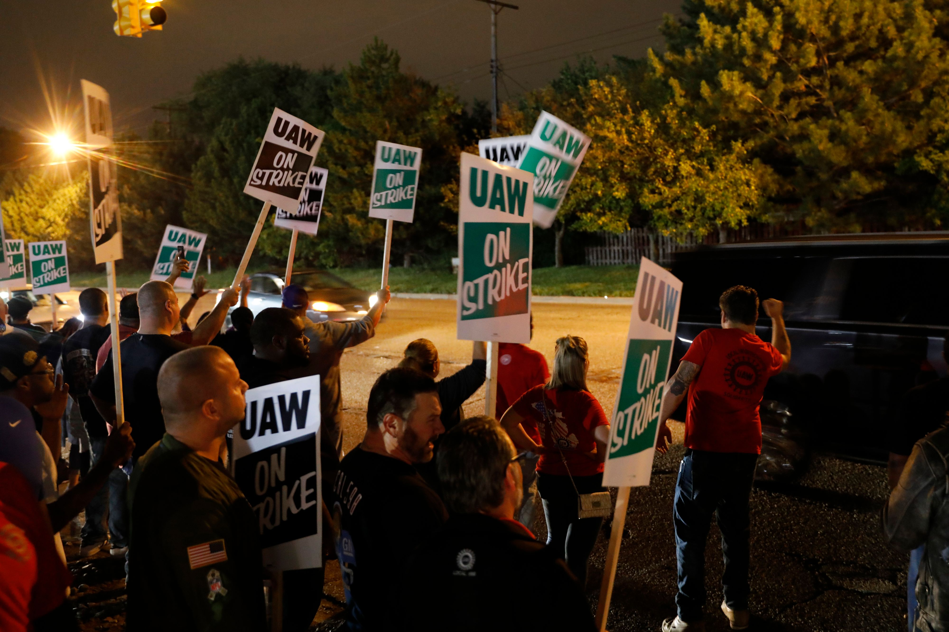 Members of the United Auto Workers (UAW) who are employed at the General Motors Co. Flint Assembly plant in Flint, Michigan, hold signs and cheer as workers drive out of the plant as they go on strike early on September 16, 2019. - The United Auto Workers union began a nationwide strike against General Motors on September 16, with some 46,000 members walking off the job after contract talks hit an impasse. (Photo by JEFF KOWALSKY / AFP) (Photo credit should read JEFF KOWALSKY/AFP/Getty Images)