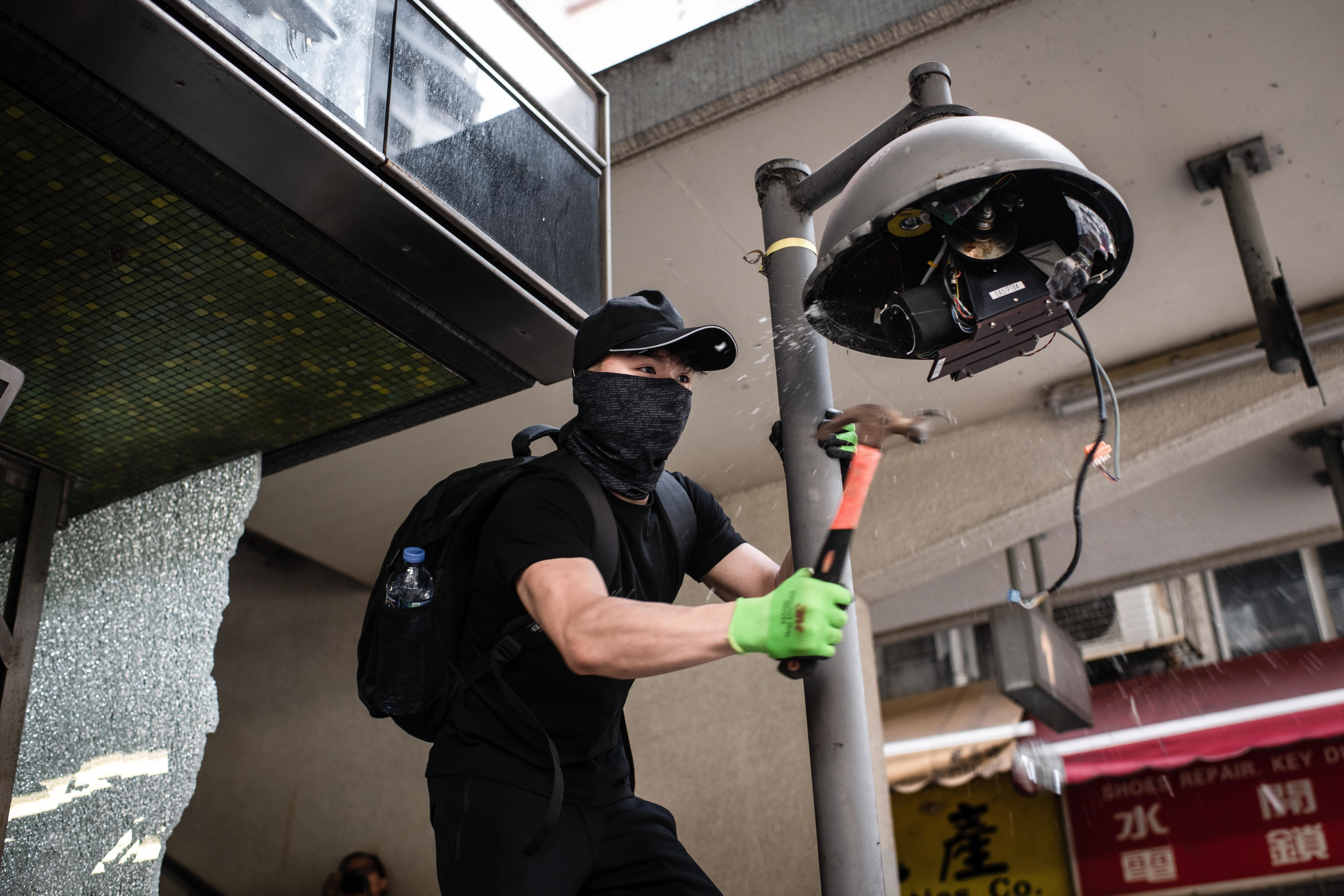 A protester destroys a surveillance camera in Hong Kong.