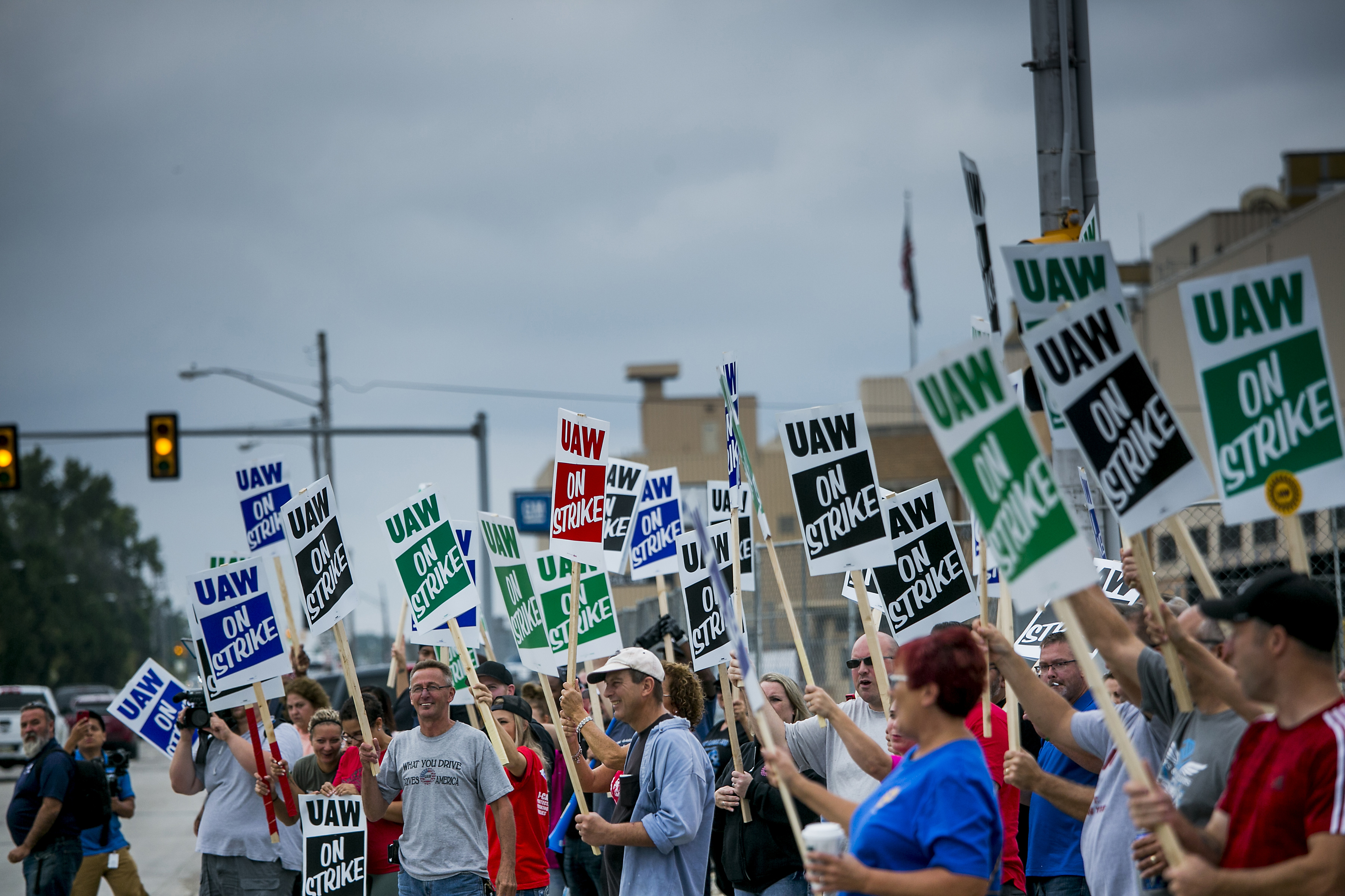 Demonstrators holds signs during a United Auto Workers (UAW) strike outside the General Motors Co. Flint Assembly plant in Flint, Michigan, U.S., on Monday, Sept. 16, 2019.