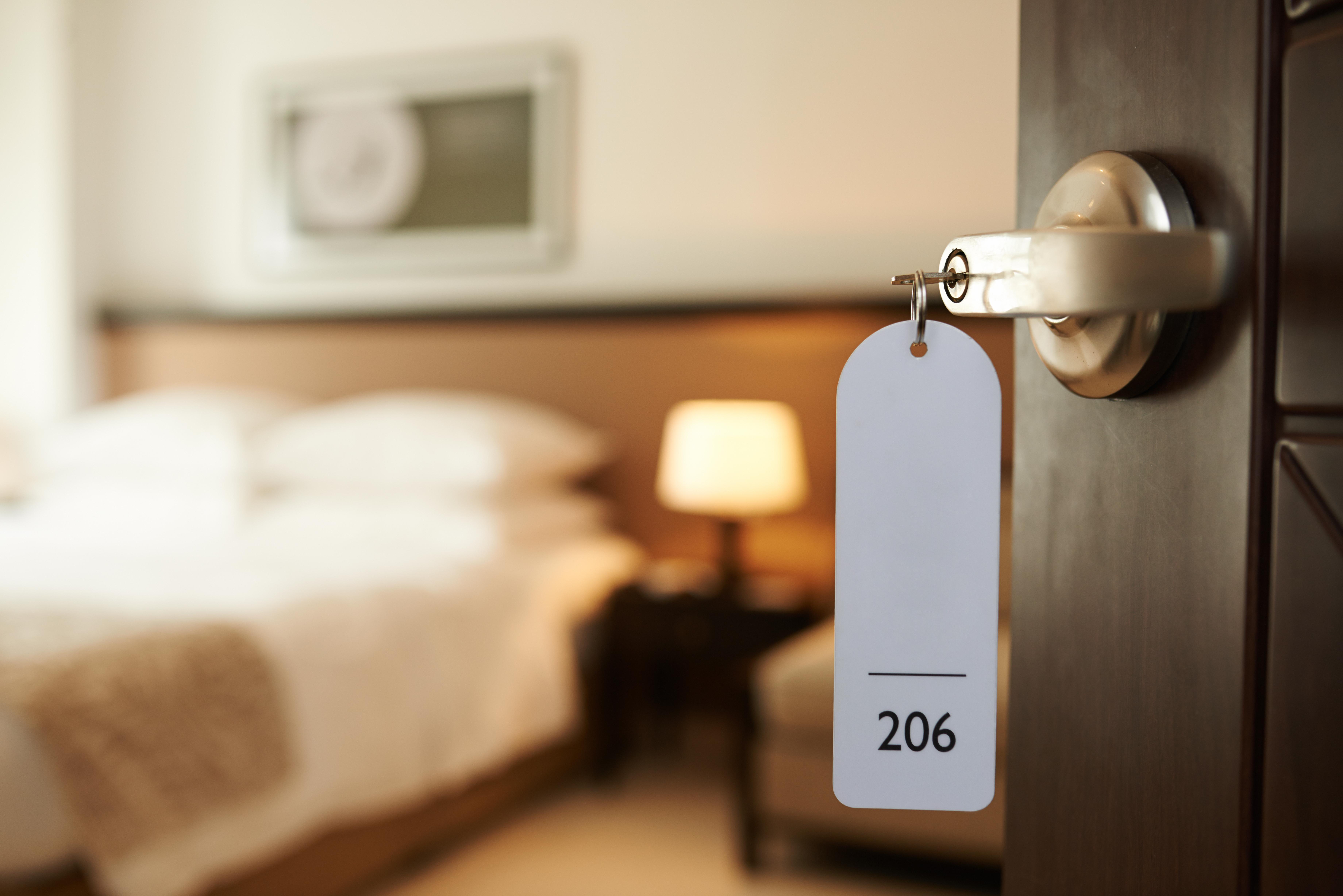 Opened door of hotel room with key in the lock.