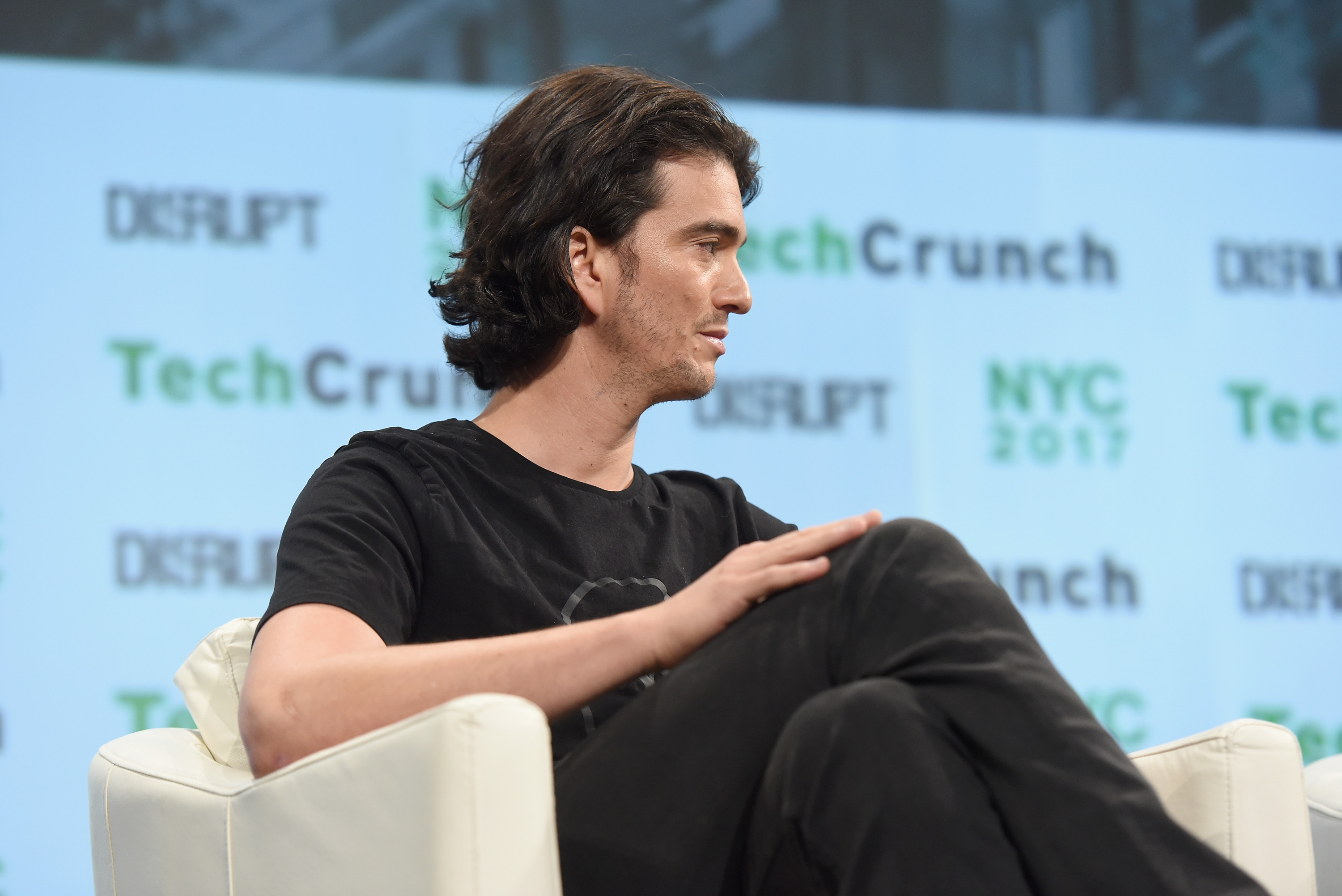 WeWork founder Adam Neumann sits in a chair turned away from the camera, showing his profile.