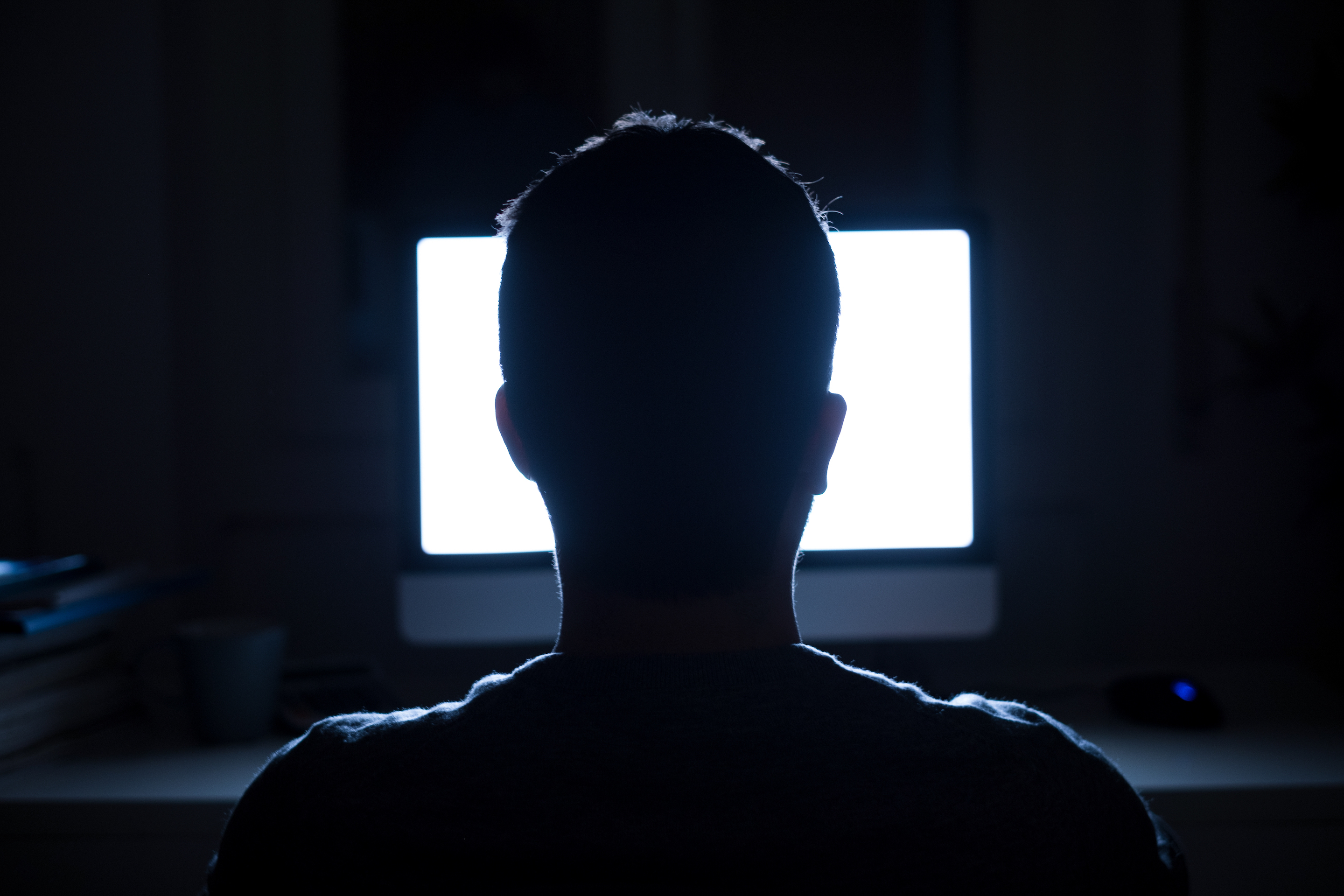 Man seated in front of computer monitor at night