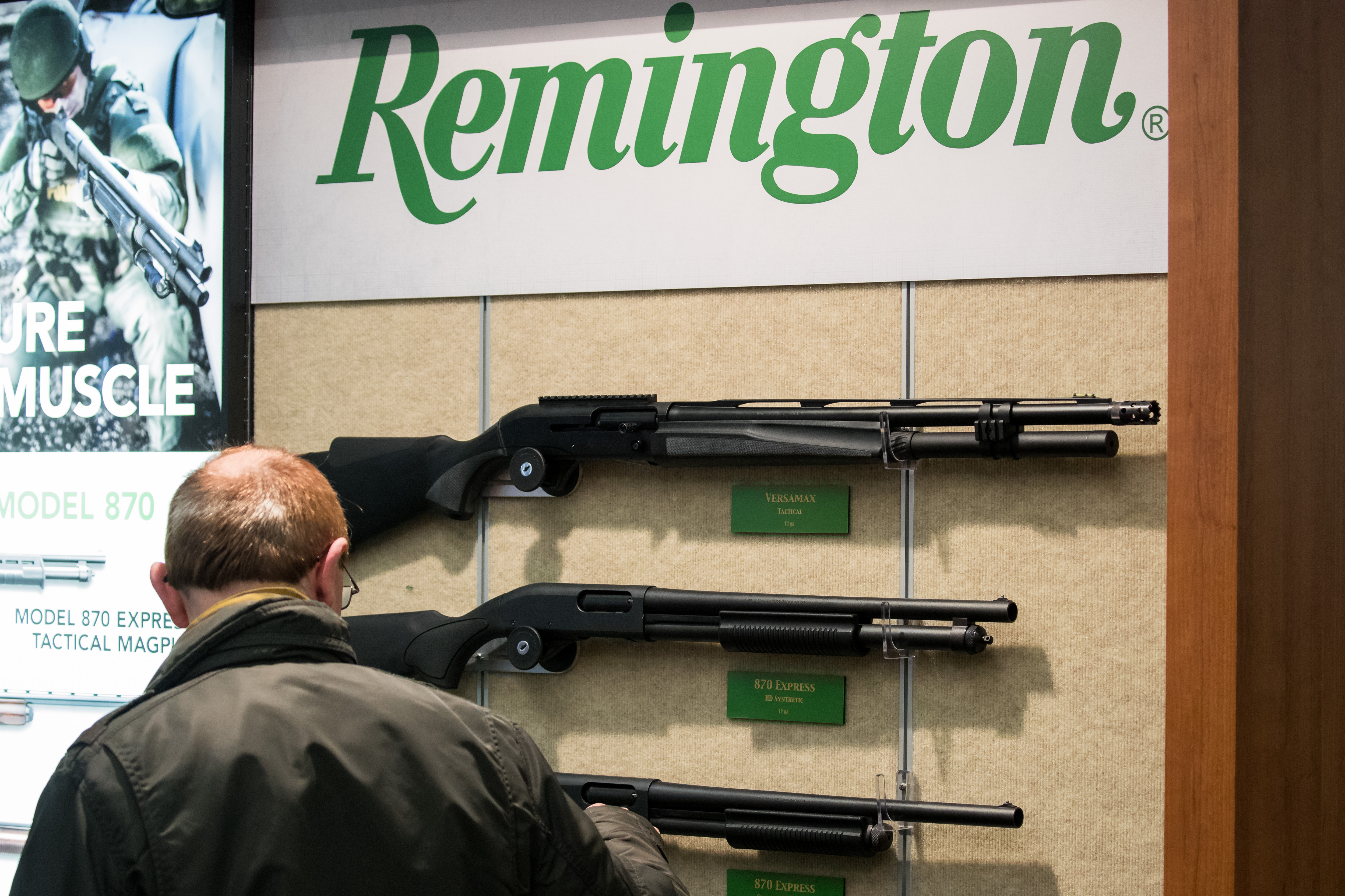 A Remington logo in green text on a white background hangs over a display of three long, black rifles. A man looks at the display.