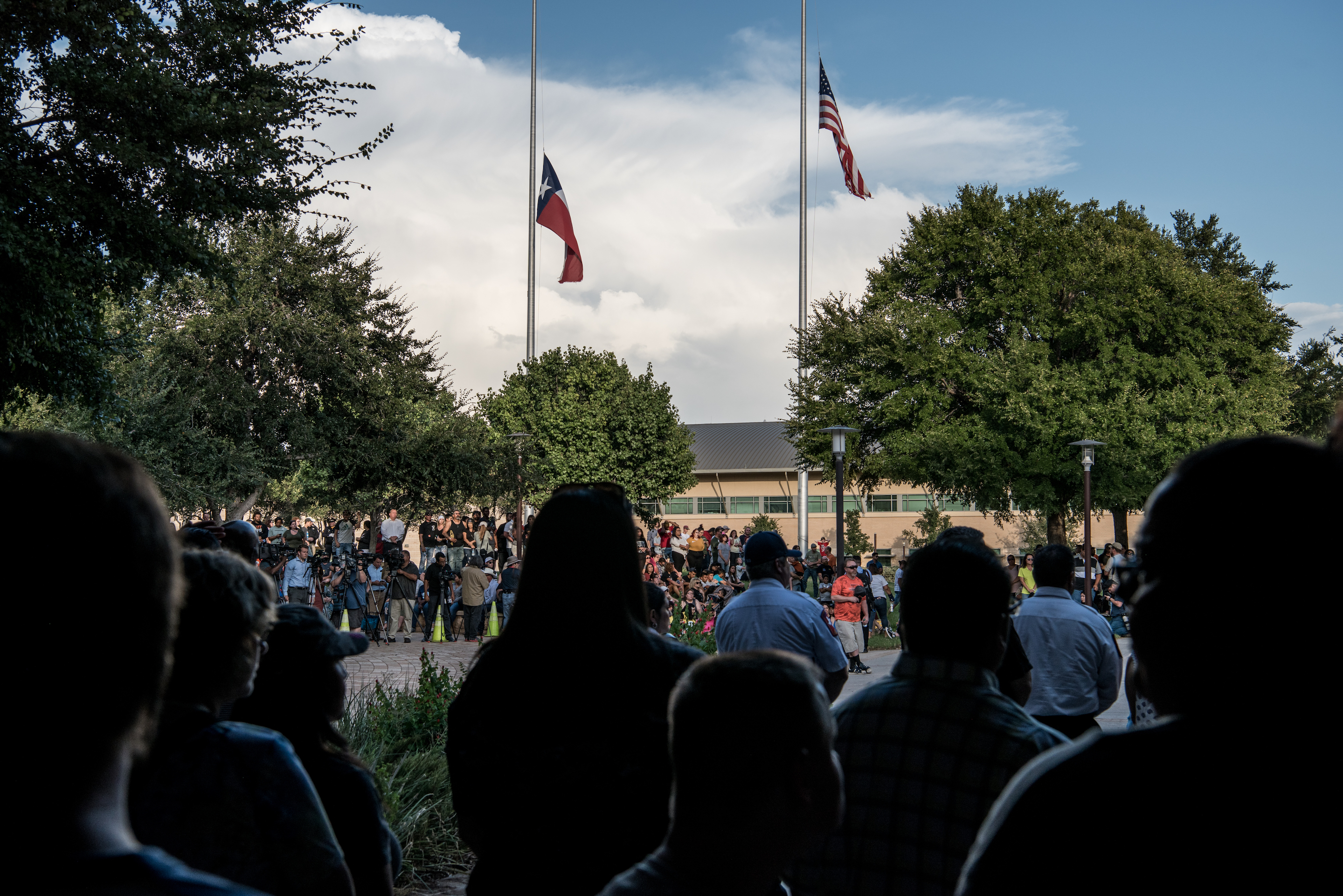 Flags fly at half mast over a prayer vigil at the University of Texas of the Permian Basin (UTPB) for the victims of a mass shooting, September 1, 2019 in Odessa, Texas.