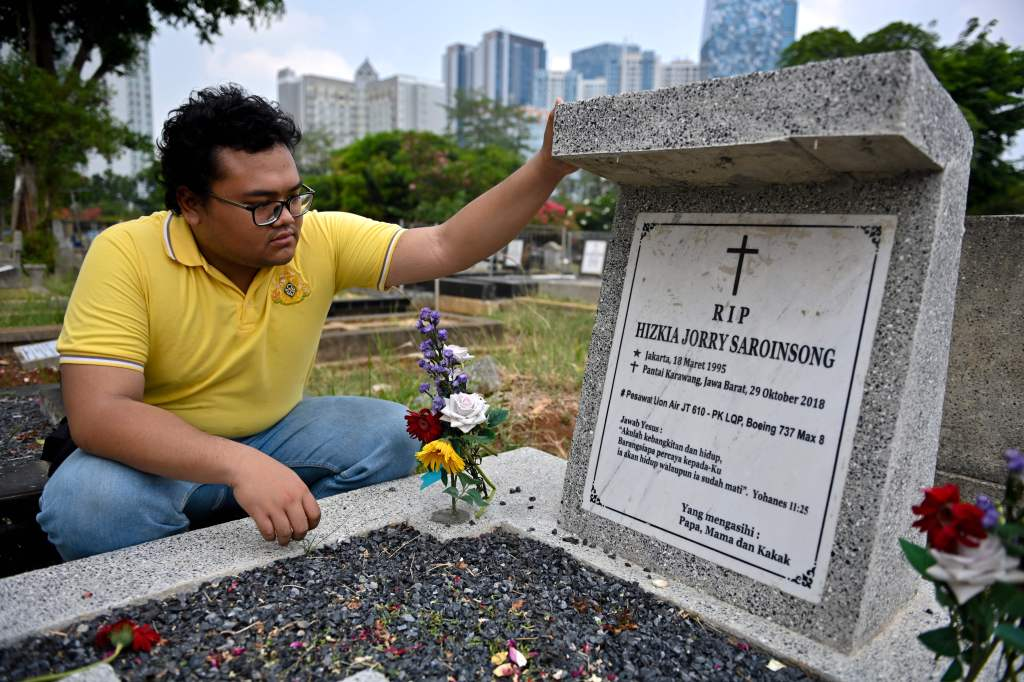 Yoda prays for his best friend who died in the Lion Air plane crash in 2018, at a cemetery in Jakarta October 29, 2019. - Grieving relatives tossed flowers into the sea on October 29 where an Indonesian Lion Air jet crashed a year ago, killing all 189 aboard, after a final accident report pointed to design flaws as a key factor in the disaster. (Photo by BAY ISMOYO / AFP) (Photo by BAY ISMOYO/AFP via Getty Images)