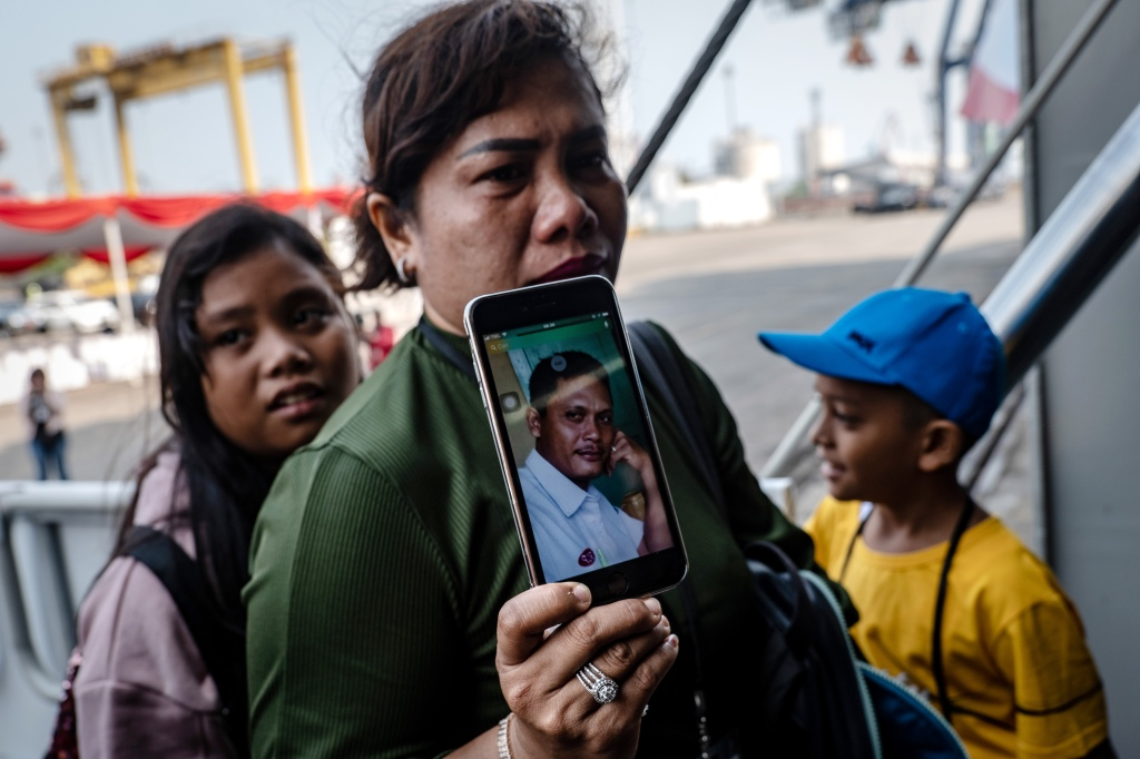JAKARTA, INDONESIA - OCTOBER 29: Dewi Manik, shows a photo of her husband, Rudy Lumbantoruan, who was a victim on board Lion Air flight JT-610 as she boards the Indonesian Navy ship KRI Semarang to visit the site where the aircraft crashed to mark the disaster's one-year anniversary at Tanjung Priok port on October 29, 2019 in Jakarta, Indonesia. Indonesians mark one year since the Lion Air crash on Tuesday as investigators said last week that a combination of aircraft design flaws, inadequate training and maintenance problems were the cause of the crash which killed all 189 people on board. Indonesian authorities added that the pilots of the Boeing 737 Max 8 plane were overwhelmed in responding to a malfunctioned flight-control system which led to its crash on October 29, 2018. (Photo by Ulet Ifansasti/Getty Images)