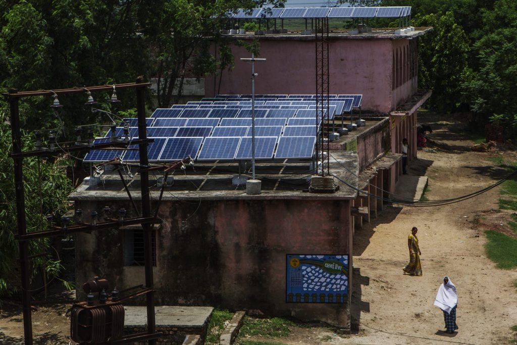 Villagers walk past solar panels mounted on the roof of a building, part of a solar power microgrid, in the village of Dharnai in Jehanabad, Bihar, India, on Thursday, July 9, 2015.