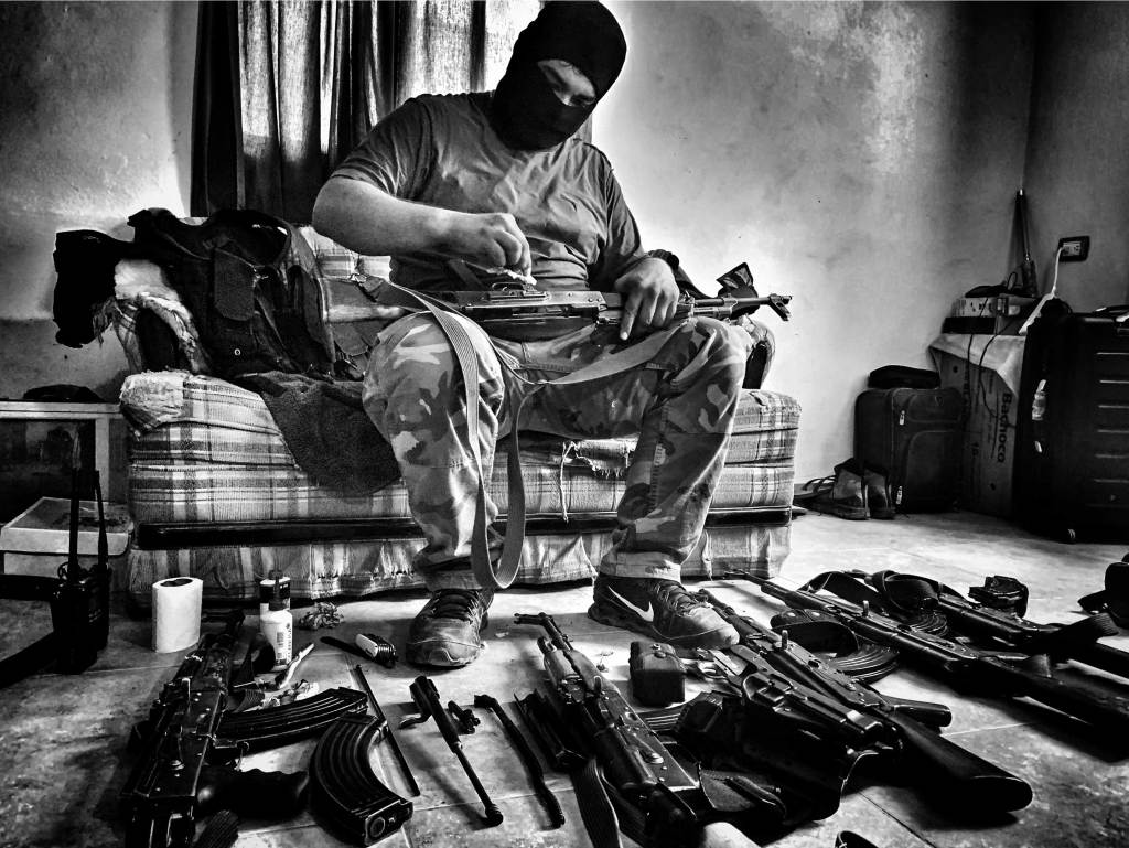 A Sinaloa Cartel member cleans guns.