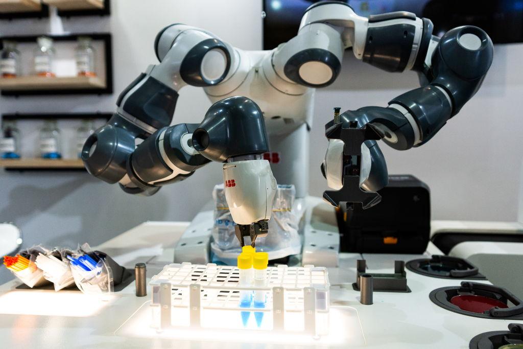 An industrial robot manipulating test tubes of liquid.