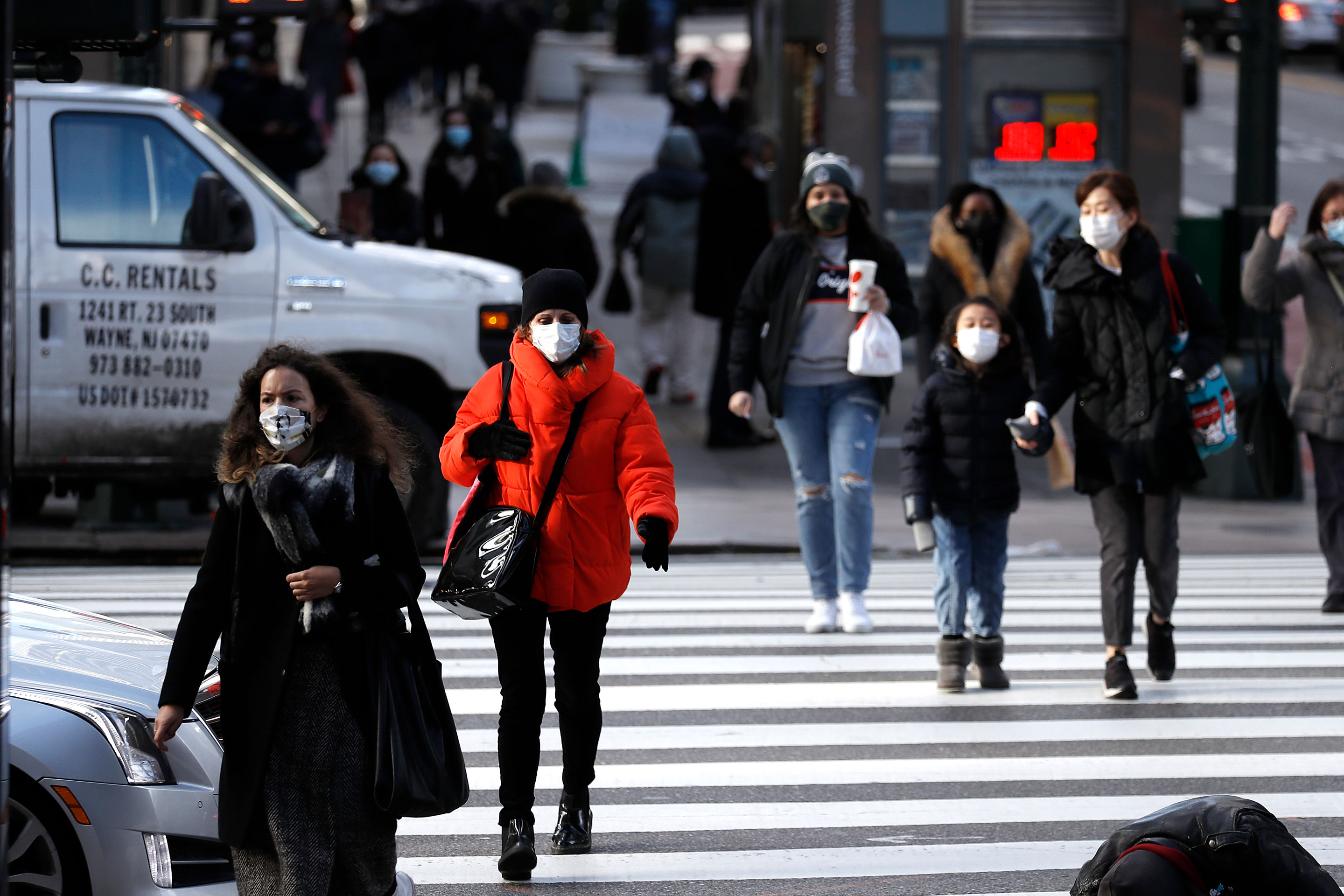 NEW YORK, NEW YORK - NOVEMBER 19: People wearing protective masks cross the street in Midtown on November 19, 2020 in New York City. The pandemic has caused long-term repercussions throughout the tourism and entertainment industries, including short-term and permanent closures of historic and iconic venues, and costing the city and businesses billions in revenue. (Photo by John Lamparski/Getty Images)