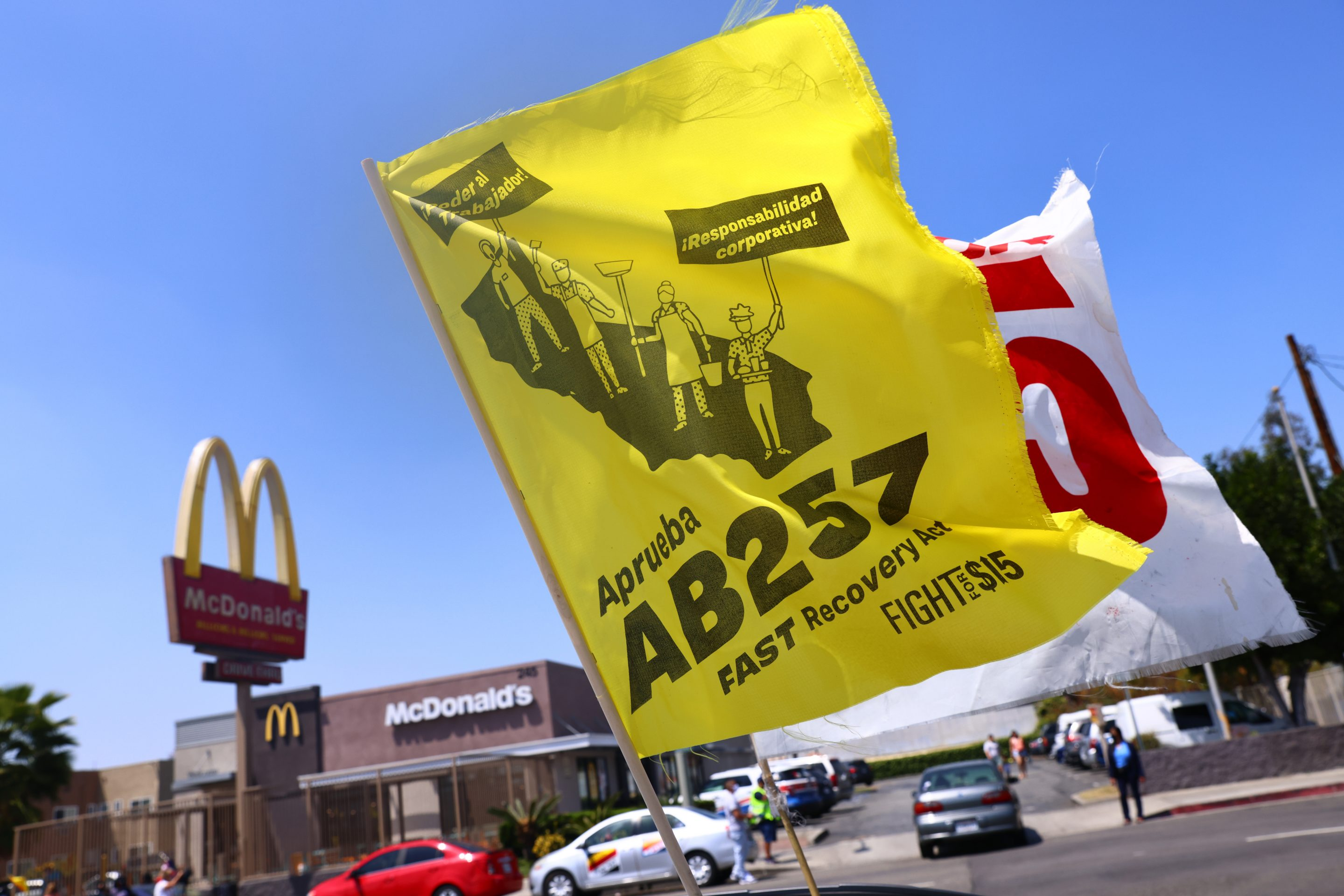 LOS ANGELES, CALIFORNIA - APRIL 16: Flags are flown at a car caravan and rally of fast food workers and supporters for passage of AB 257, a fast-food worker health and safety bill, on April 16, 2021 in the Boyle Heights neighborhood of Los Angeles, California. The rally was held outside of a McDonald's location where a worker lodged public health complaints and a wage theft complaint. Some fast food workers are on strike in Los Angeles County today in support of the bill. (Photo by Mario Tama/Getty Images)