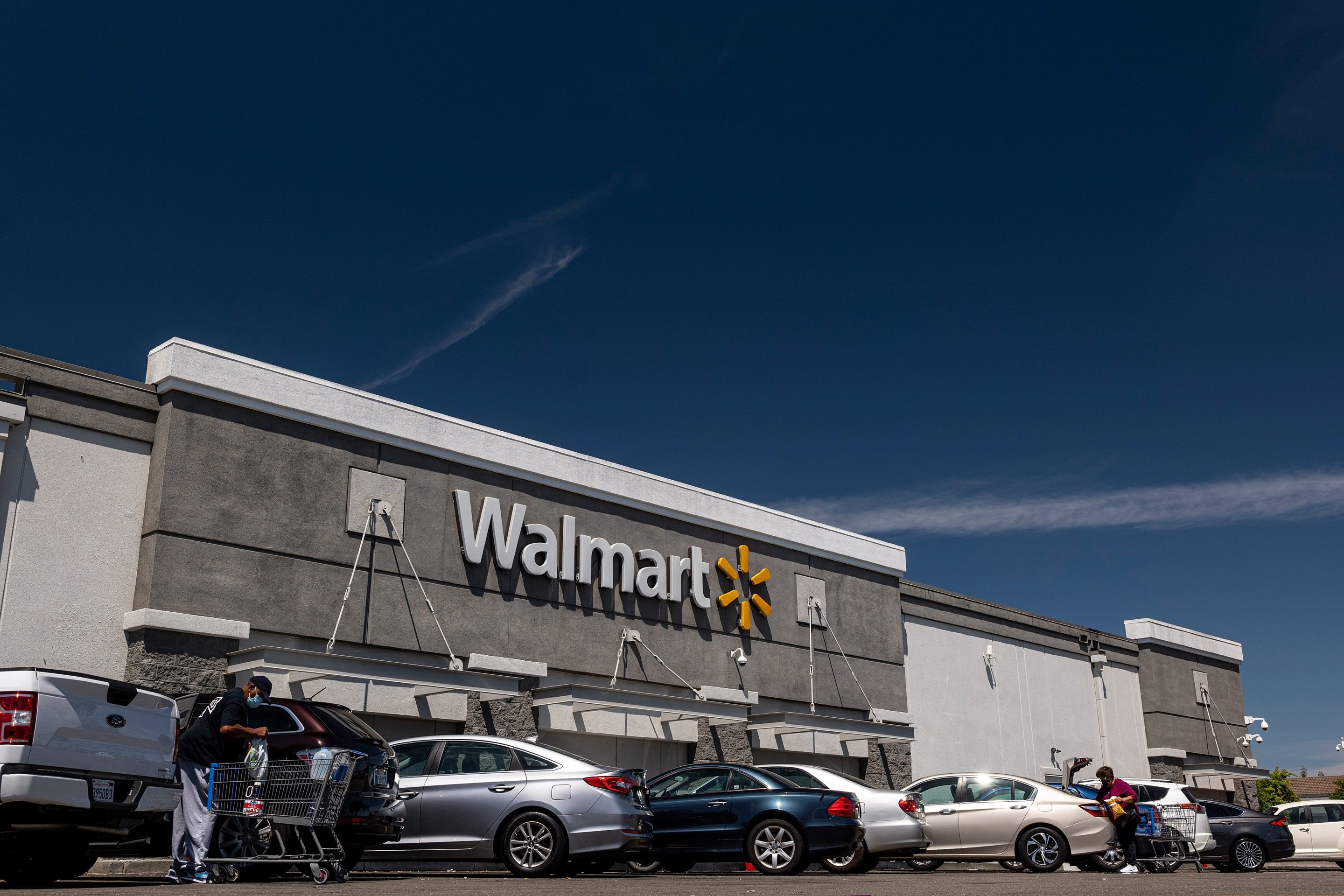 Shoppers load items into their vehicles outside a Walmart store in San Leandro, California, U.S., on Thursday, May 13, 2021. Walmart Inc. is expected to release earnings figures on May 18. Photographer: David Paul Morris/Bloomberg via Getty Images